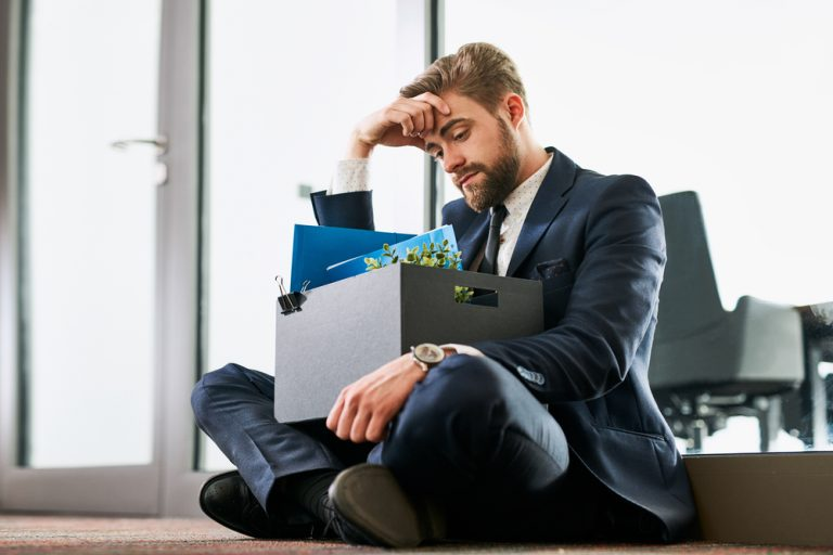 Man sitting on the floor with his personal effects after losing his job